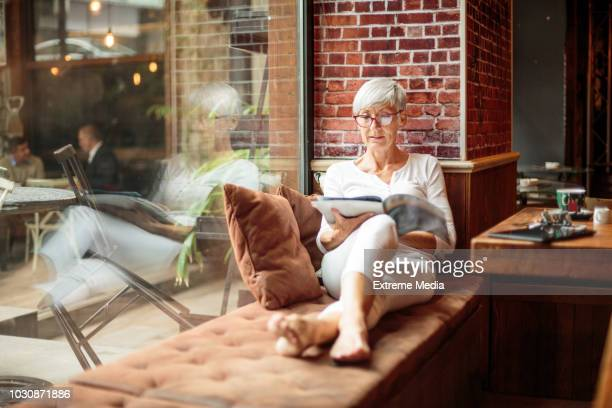 senior woman reading magazine in cafeteria - magazine stock pictures, royalty-free photos & images
