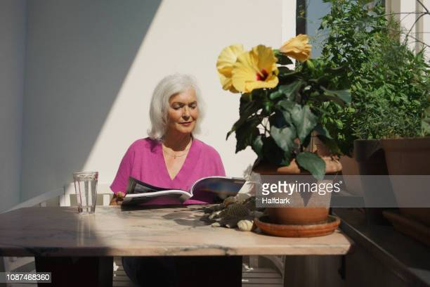 senior woman reading magazine on sunny patio - einfaches leben stock-fotos und bilder