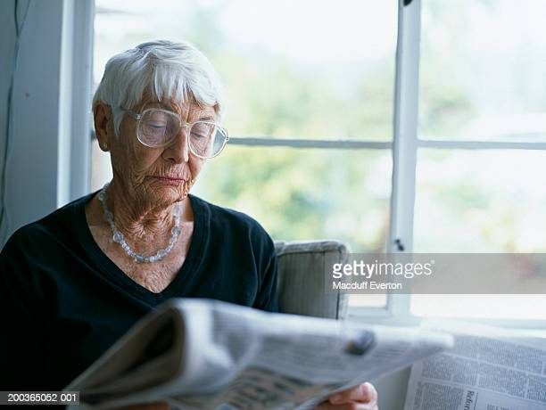 senior woman reading newspaper by window (focus on face) - everton women stock pictures, royalty-free photos & images