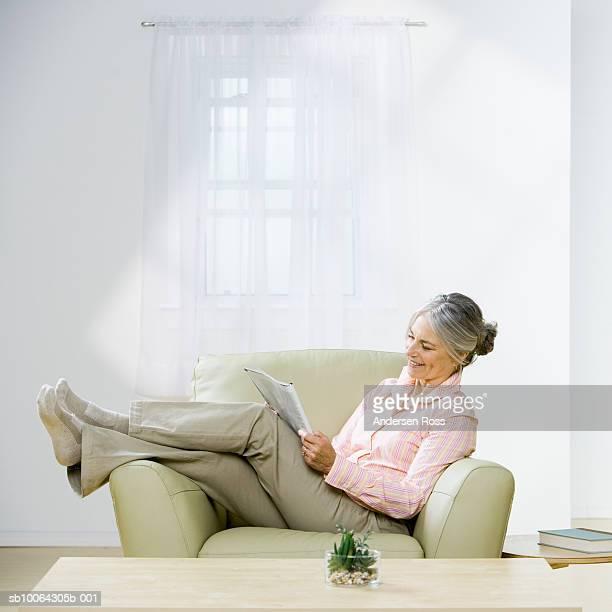 Senior woman reading newspaper in armchair