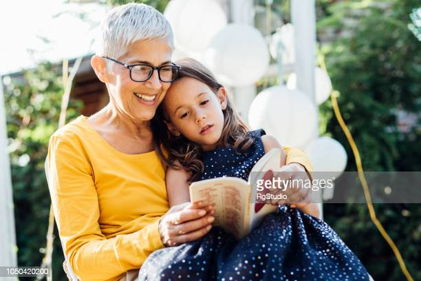 senior woman reading to granddaughter - cottage exterior stock pictures, royalty-free photos & images