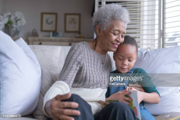 Senior woman reading with her granddaughter