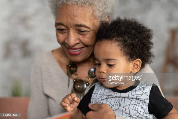 senior woman reading with her grandson - fat granny stock pictures, royalty-free photos & images