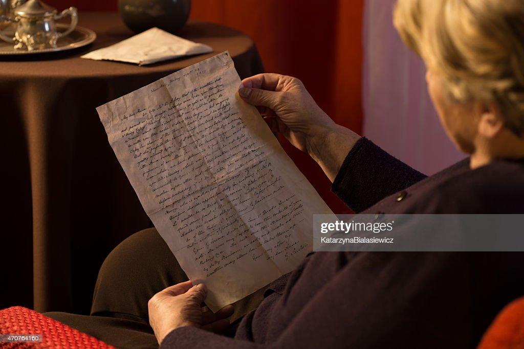 Senior woman reading yellowed letter : Stock Photo