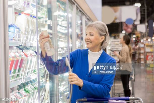 Senior woman reads dairy label in grocery store