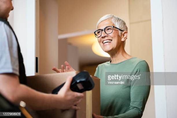 senior woman received package from courier - receiving stock pictures, royalty-free photos & images