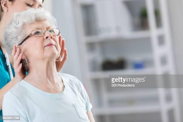 Ältere Frau erhält Kopfmassage von Chiropraktiker