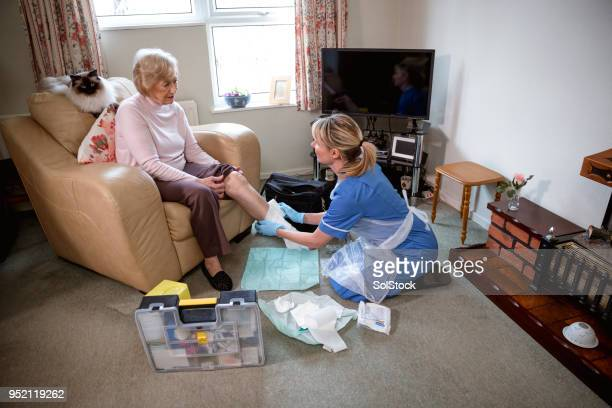 senior woman receives medical care at home - old lady feet stock pictures, royalty-free photos & images