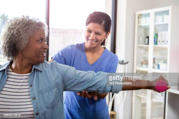 senior woman receives physical therapy for arm injury - physical therapist stock pictures, royalty-free photos & images