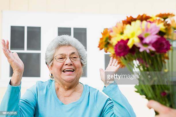senior woman receiving a bouquet - receiving stock pictures, royalty-free photos & images