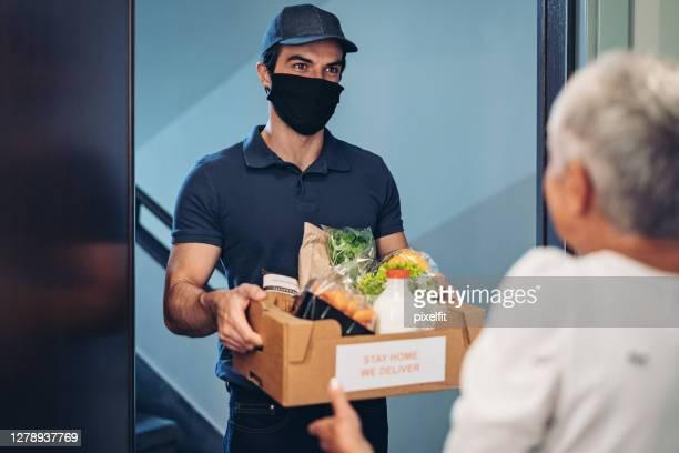 idosa recebendo uma entrega de comida em sua porta - receber - fotografias e filmes do acervo