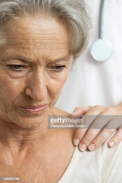 Senior woman receiving bad news from caring doctor, cropped