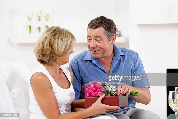 Senior Woman Receiving Chocolate And Flowers From Partner