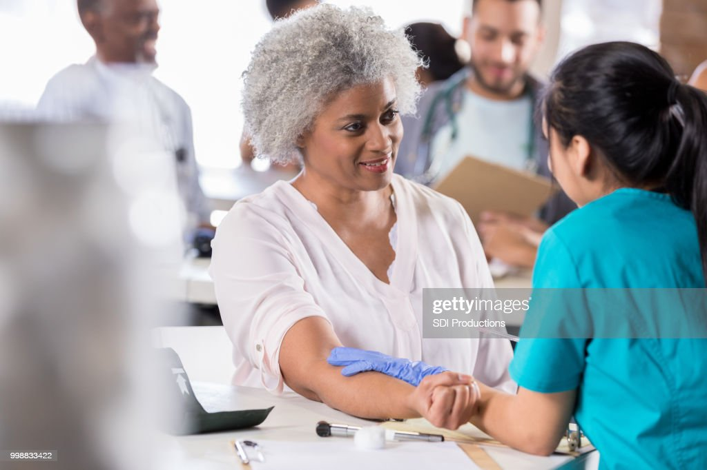 Senior woman receiving flu vaccine : Stock Photo