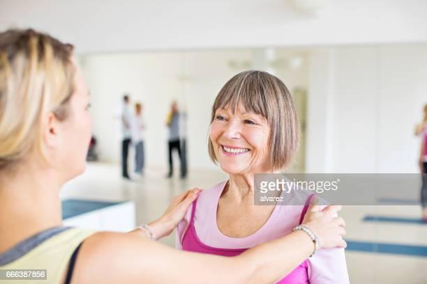Senior woman receiving shoulder massage from coach