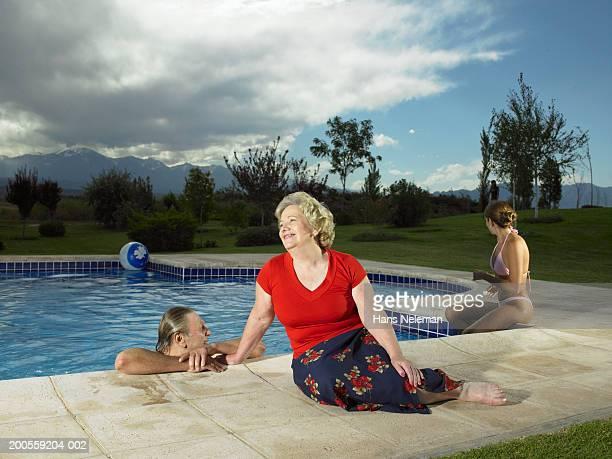 Senior woman reclining at edge of pool, senior man and woman in pool