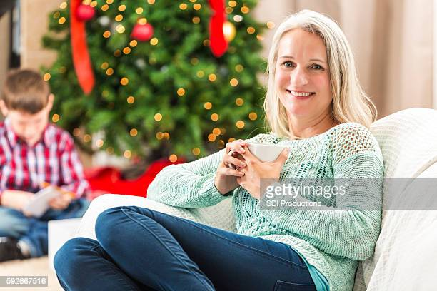 Senior woman relaxes on sofa st Christmastime
