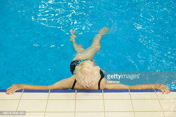 senior woman relaxing at side of pool, elevated view - alte frau badeanzug stock-fotos und bilder