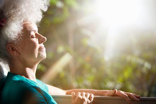 senior woman relaxing by window in sunlight - gettyimageskorea