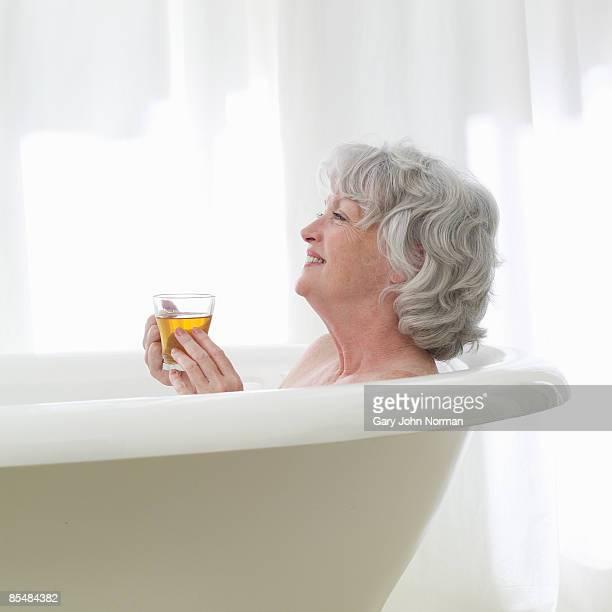 Senior woman relaxing in bath holding tea