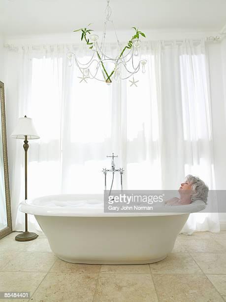Senior woman relaxing in bath.