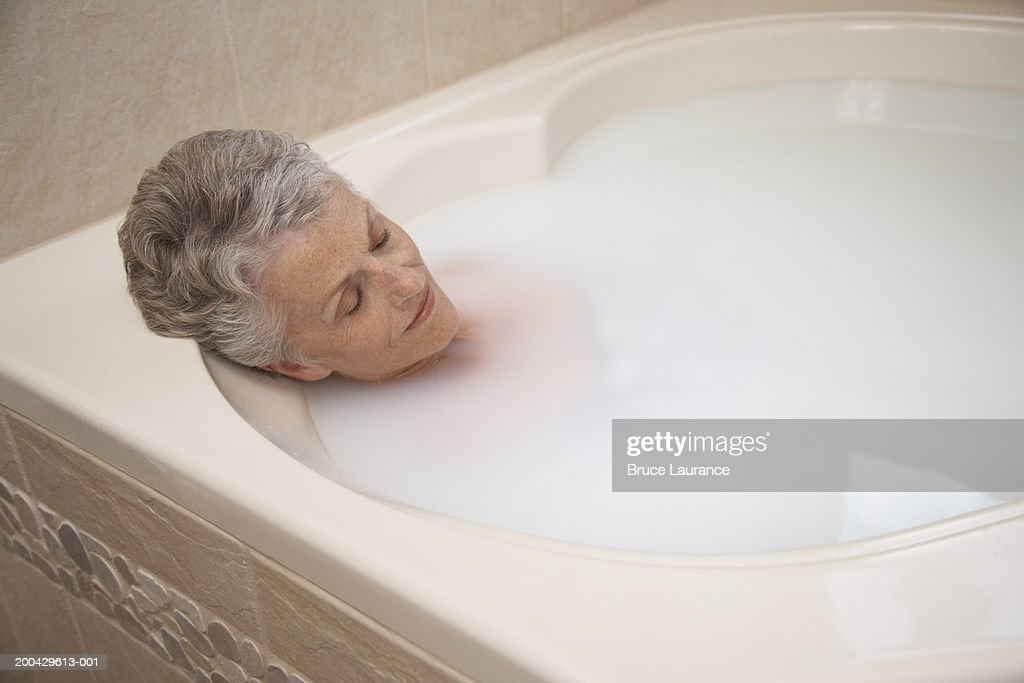 Senior Woman Relaxing In Bath Tub Stock Photo | Getty Images