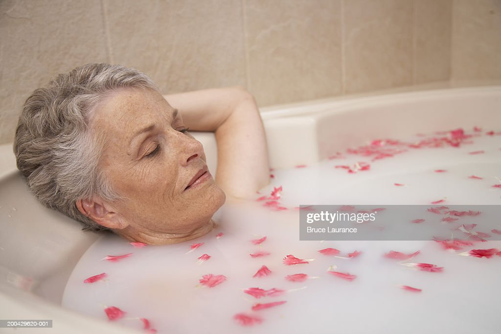 Senior Woman Relaxing In Bath Tub With Flower Petals Stock Photo ...
