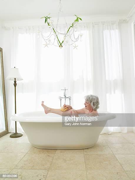 Senior woman relaxing in bath washing with sponge