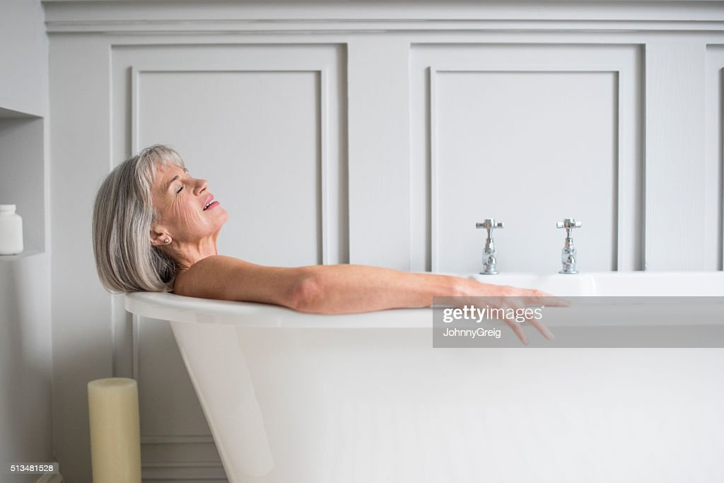 Senior woman relaxing in bath with eyes closed : Stock Photo