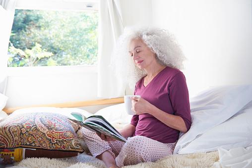 senior woman relaxing in bedroom drinking coffee - gettyimageskorea