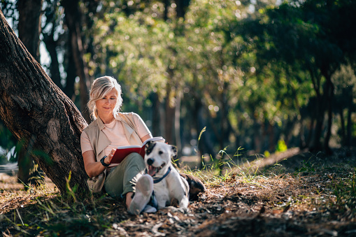 Senior woman relaxing in nature with book and pet dog 979327762
