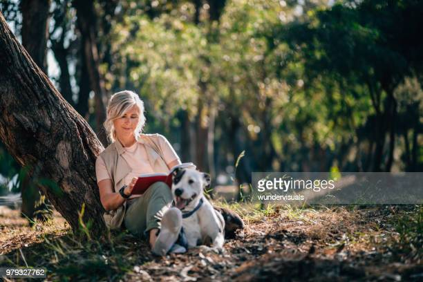 senior woman relaxing in nature with book and pet dog - taking a break stock photos and pictures