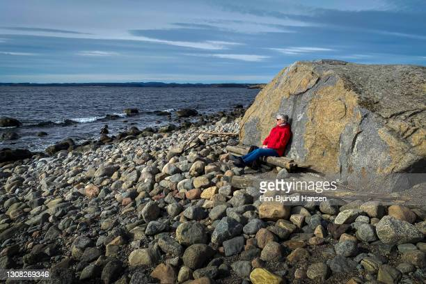 senior woman relaxing in the sun on the beach of molen in vestfold norway - finn bjurvoll stock-fotos und bilder