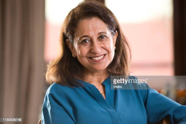 senior woman relaxing on chair at home - indian ethnicity stock pictures, royalty-free photos & images