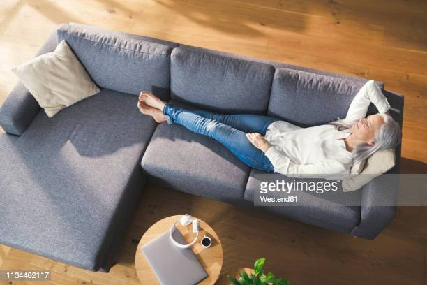 senior woman relaxing on couch - one senior woman only stock pictures, royalty-free photos & images