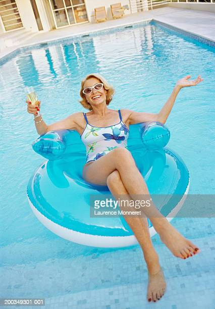 Senior woman relaxing on float in swimming pool, portrait