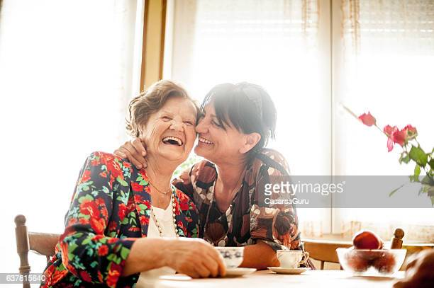 senior woman relaxing with her daughter at home - old stock photos and pictures