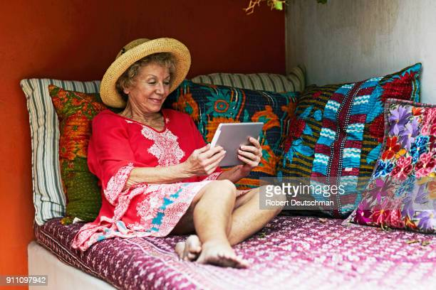 senior woman relaxing with iPad on vacation