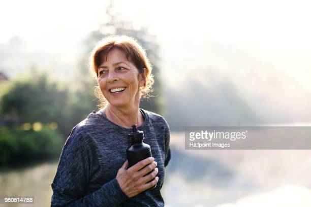 senior woman resting after exercise outdoors in nature in the foggy morning. copy space. - ochtend stockfoto's en -beelden