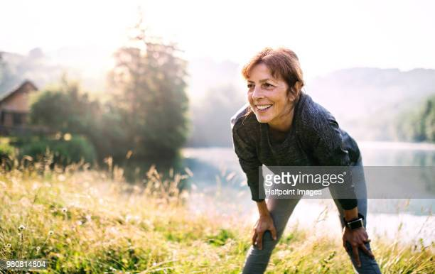 senior woman resting after exercise outdoors in nature in the foggy morning. copy space. - active lifestyle stock pictures, royalty-free photos & images