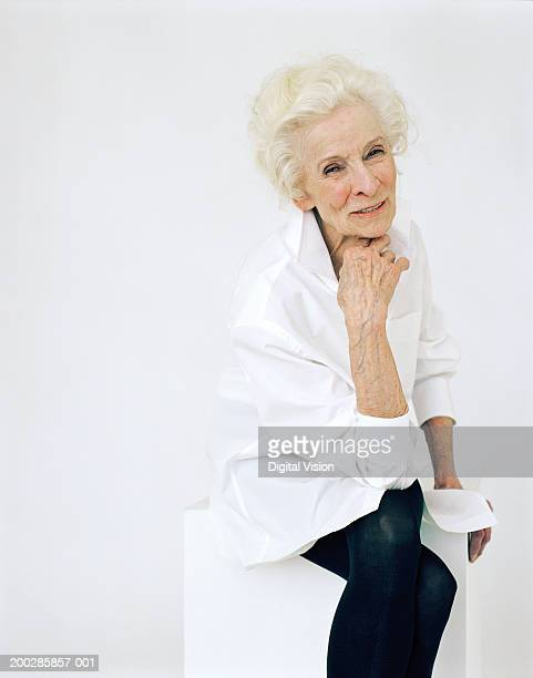 senior woman resting chin on hand, smiling, portrait - old women in pantyhose stock photos and pictures