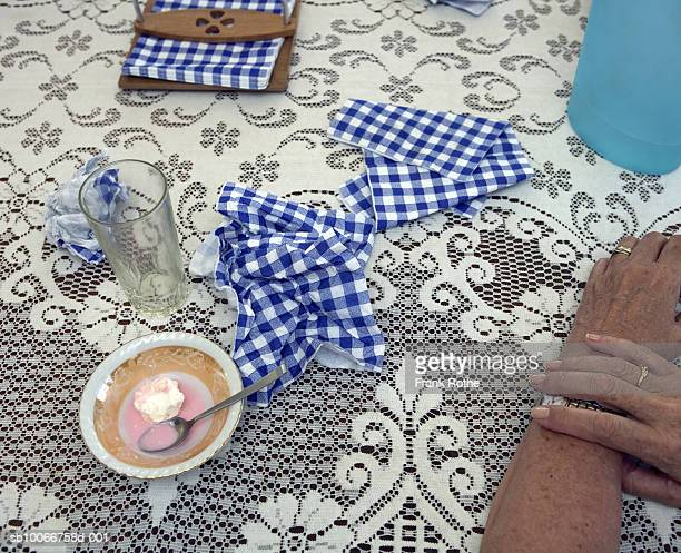Senior woman resting hands on table with lace tablecloth after meal