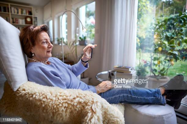 Senior woman resting in armchair at home holding cell phone