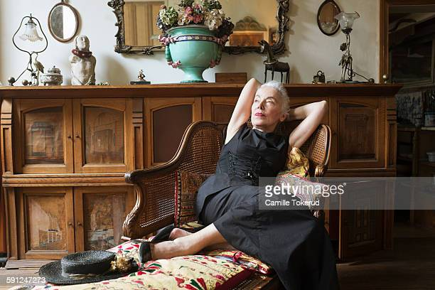 Senior woman resting on antique chair thinking