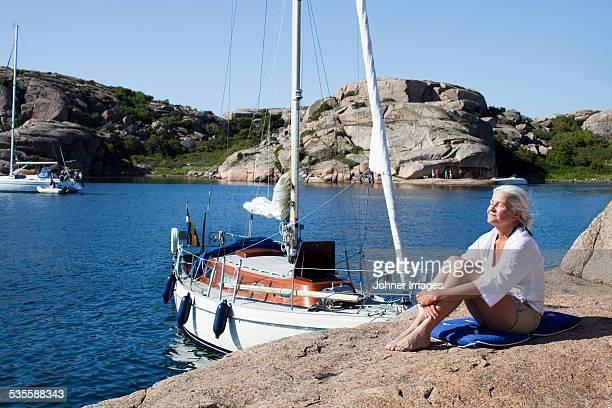 Senior woman resting on cliff