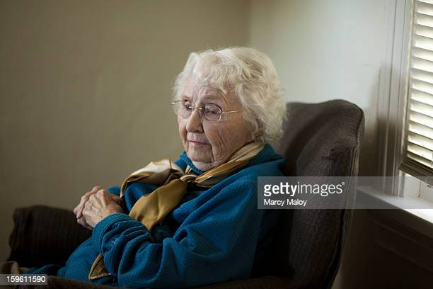 Senior woman resting somberly in a chair.