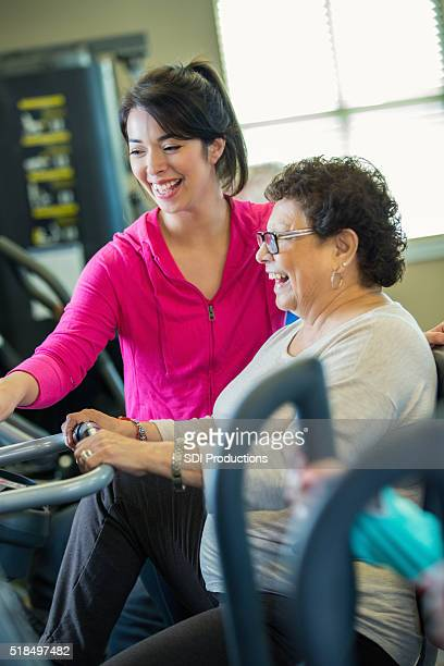 Senior woman rides stationary bicycle