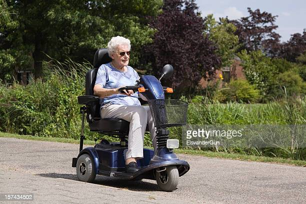 senior woman riding an electric scooter - mobility scooter stock photos and pictures