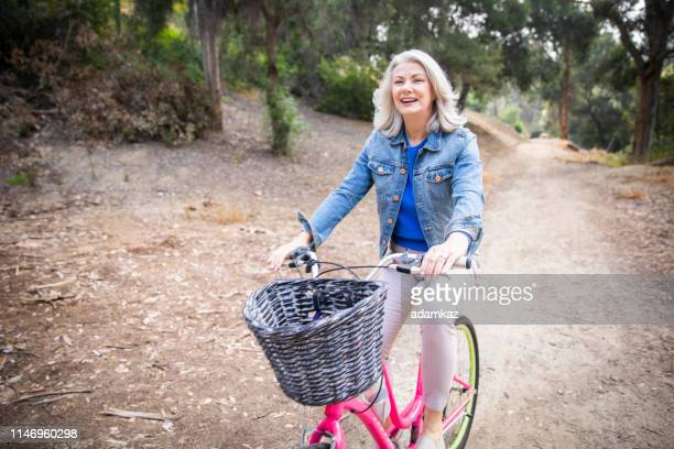 senior woman riding bicycle in nature - women's issues stock pictures, royalty-free photos & images
