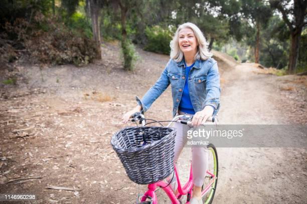 senior woman riding bicycle in nature - questão da mulher imagens e fotografias de stock